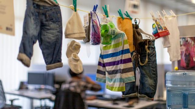 Babykleider an einer Wäscheleine in einem Büro.