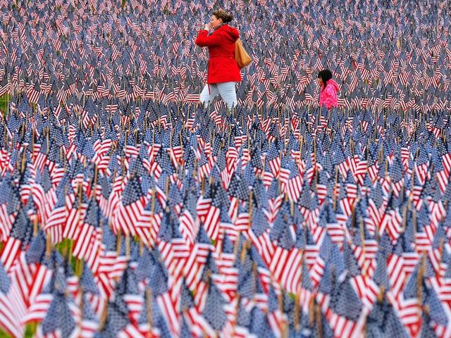 Ein Meer aus US-Flagen, darin eine Frau und ein Kind.