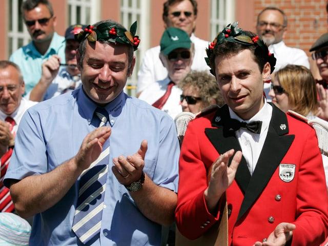 Zwei applaudierende Männer mit Lorbeerkränzen auf dem Kopf.