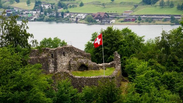 Burgruine mit Schweizerfahne und See im Hintergrund.