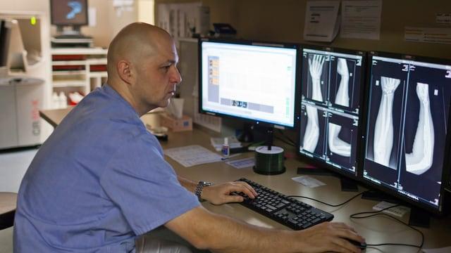 Ein Arzt schaut in drei verschiedenen Bildschirme auf denen Daten und Rötgenbilder zu sehen sind.