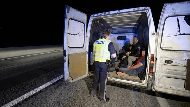 Ein Polizist steht vor einem Lieferwagen mit Migranten drin.
