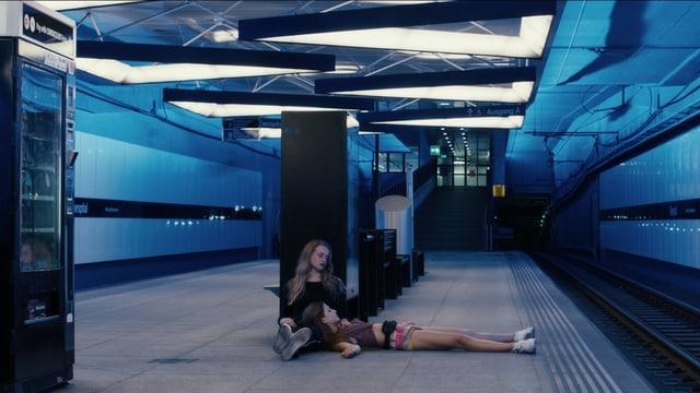 Zwei Mädchen am Boden in einem unterirdischen Bahnhof.