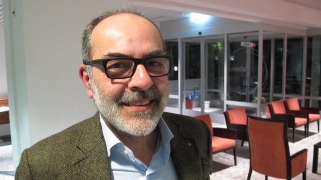 Diego Faccani mit Bart und Brille lacht freundlich in die Kamera.