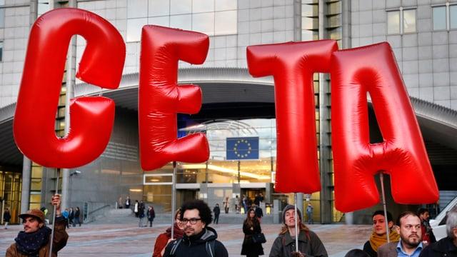 Personen halten die roten Letter C E T A hoch.