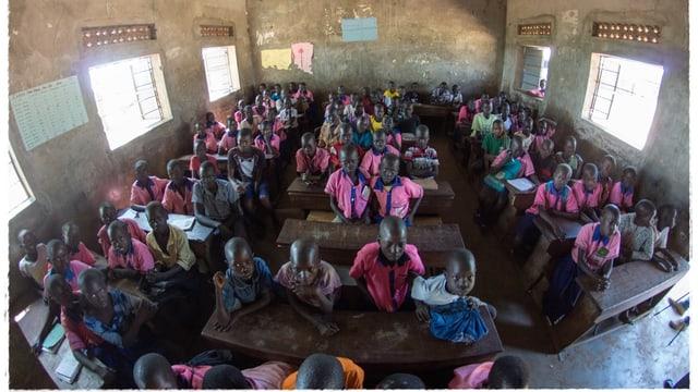 Überfülltes Schulzimmer in Uganda, fröhliche Gesichter
