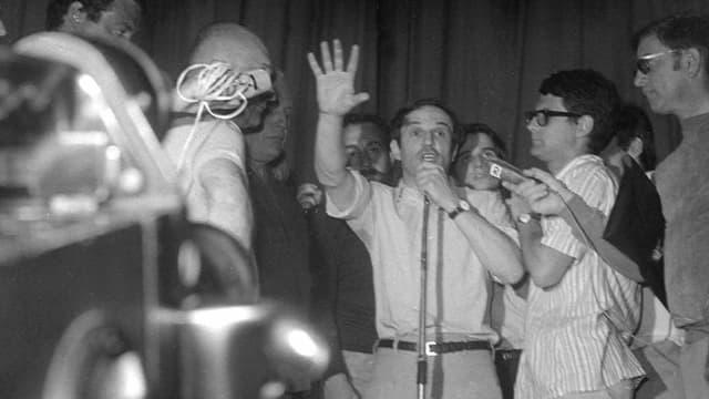 François Truffaut steht am Mikrofon mit erhobener Hand, Reporter halten ihre Mikrofone hin.