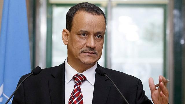 Scheich Ahmed steht am Rednerpult hinter zwei Mikrofonen