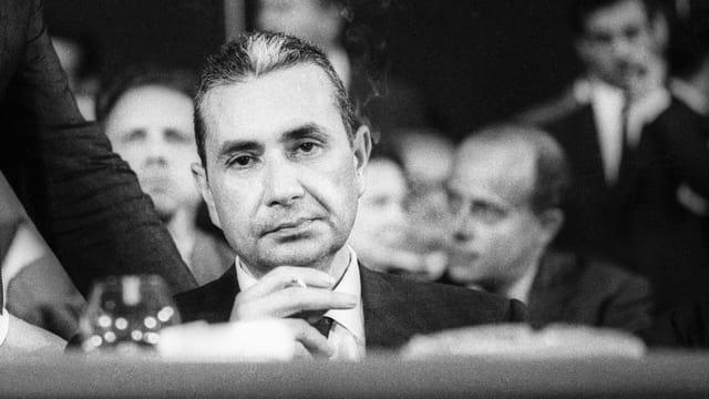 Ein Mann im Anzug und Zigarette in der Hand sitzt mit leerem Blick an einem Tisch, hinter ihm sitzen weitere Männer.