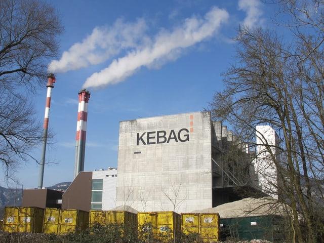Ein grosses Gebäude aus Beton mit drei Kaminen, aus welchen Rauch aufsteigt.