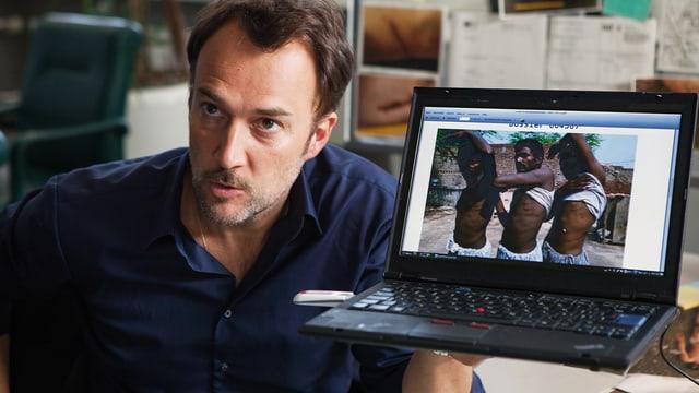 Ein Mann hält einen Laptop in die Kamera. Auf dem Bildschirm seind drei dunkelhäutige Männer zu sehen, die sich das T-Shirt hochgekrempelt haben.
