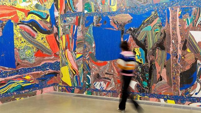 Eine Museumsbesucherin läuft durch einen bunten Raum.