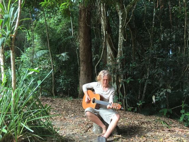 Jogl sitzt mit Gitarre im Regenwald.