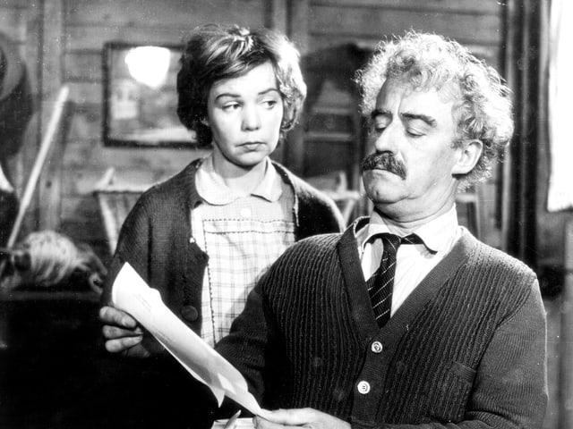 Ein männlicher Schauspieler verwundert auf einen Zettel. Eine Frau im Hintergrund schaut den Mann an.