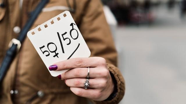 Frau hält Zettel mit der Aufschrift 50/50 in die Luft