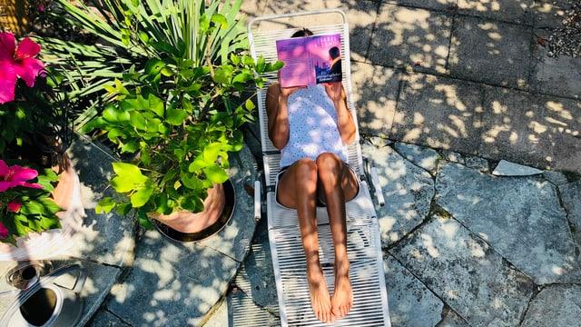 Annette König liegt auf einem Spaghetti-Liegestuhl und liest «Ein unvergänglicher Sommer» von Isabel Allende