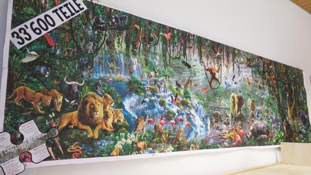 An einer Wand aufgehängte Vorlage des Puzzles: Viele Tiere in einer Urwaldlandschaft.