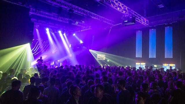 Eine Menschenmenge vor einer Bühne die von farbigen Scheinwerfern erleuchtet wird.