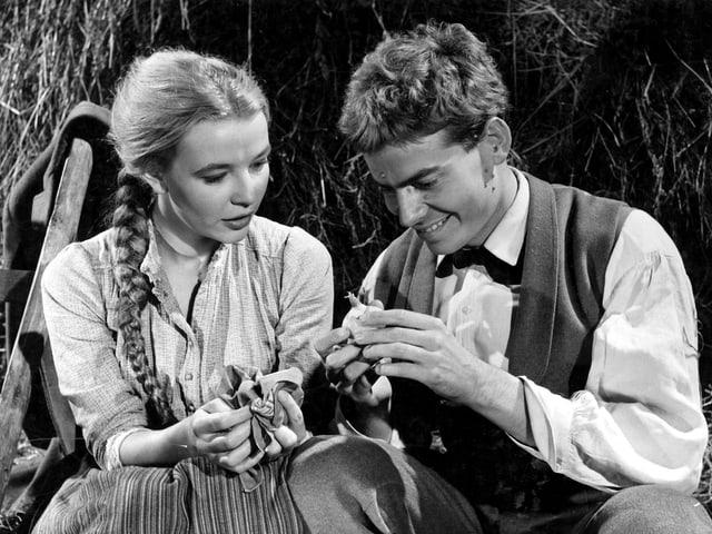 Szene aus Anne Bäbi Jowäger. Ein junger Mann und eine junge Frau sitzen nebeneinander. Der Mann hält etwas in den Händen und zeigt es der Frau.
