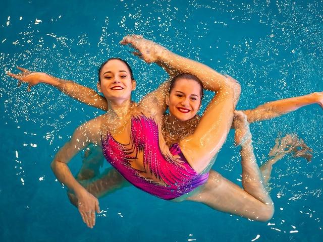 Zwei Synchronschwimmerinnen posieren im Wasser.