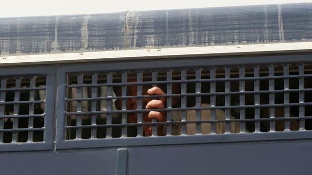 Ein Gefangener sieht zwischen Gitterstäben hindurch