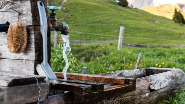 Ein Brunnen. Wasser läuft aus dem Wasserhahnen.