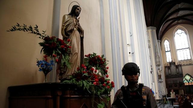 Bewaffneter Polizist steht vor Jesusstatue