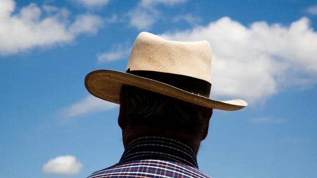 Ein weisser Strohhut mit schwarzer Krempe, getragen von einem Mann (er ist von hinten fotografiert).
