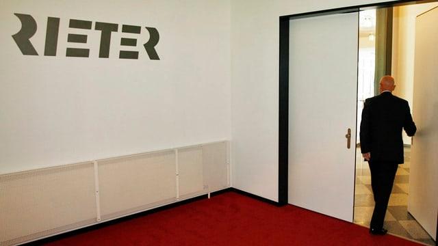 Verwaltungsratspräsident Erwin Stoller beim Verlassen eines Zimmers mit dem Rieter-Logo an der Wand.