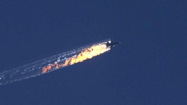 Ein Flugzeug zieht eine Spur aus Flammen hinter sich her.