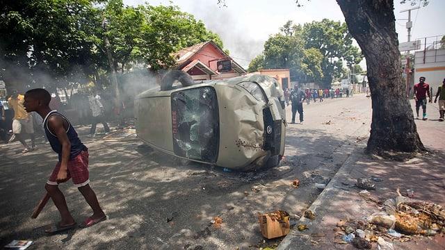 Umgestürztes Auto, dazwischen Männer.
