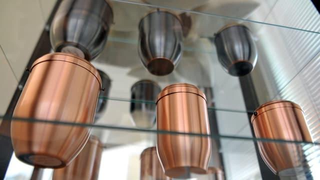 Mehrere Urnen aus Metall in einem Regal.