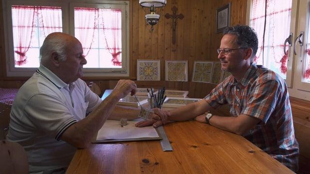 Zwei Männer sitzen an einem Tisch. Einer hält ein Pendel in der Hand.