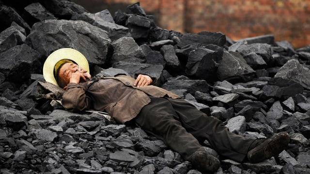 Mann ruht sich auf Kohlehaufen aus.