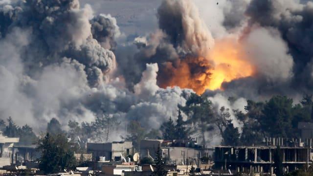 Eine Explosion und Rauch steigen über Häusern auf