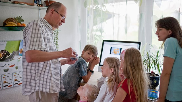 Ein Lehrer gibt seinen Schülerinnen eine Erklärung.
