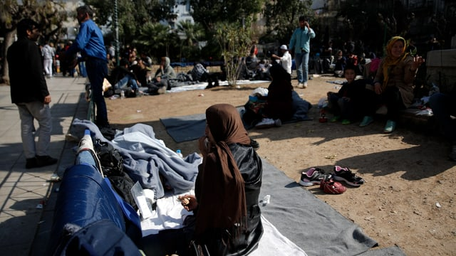 Flüchtlinge sitzen am Boden