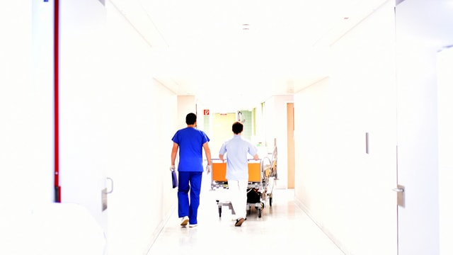 Arzt und Krankenschwester schieben ein Bett durch einen Gang.