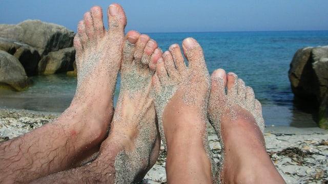 Männliches und weibliches Fusspaar mit Sand, im Hintergrund das Meer.