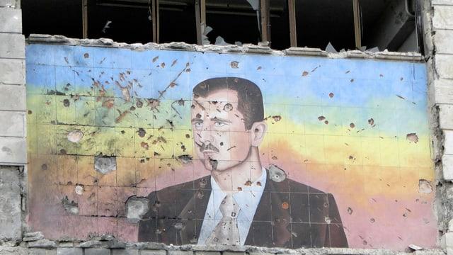 Ein Wandbild von Assad mit Einschlusslöchern