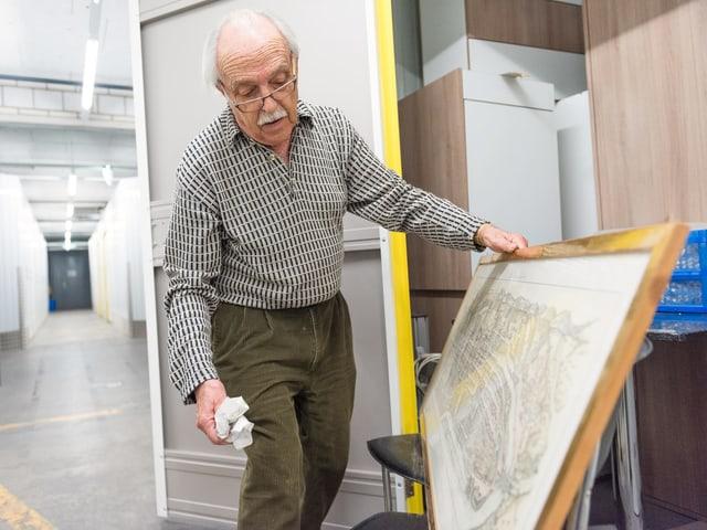 Ein Mann hält ein Bild in der Hand.