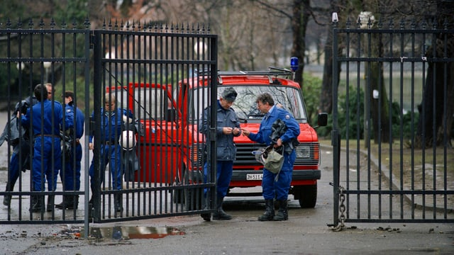 Halboffenes vergittertes Parktor, dahinter Polizeifahrzeug und mehrere Beamte in Kampfmontur