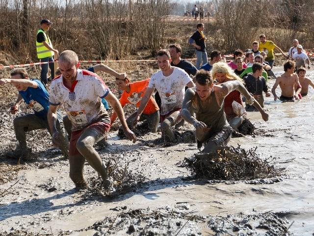 Teilnehmer am Survival Run in einem Schlammtümpel.
