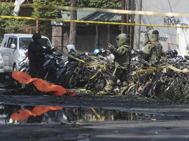 Polizisten vor zerstörten Motorrädern