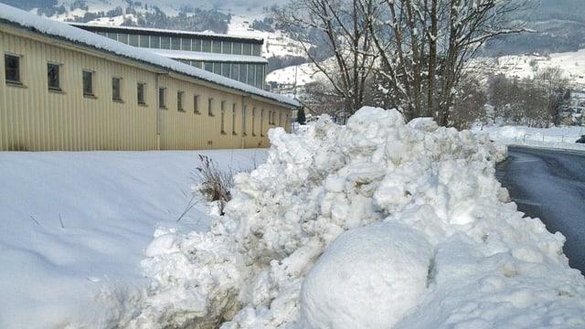 Eine Strasse mit Schnee am Rand.