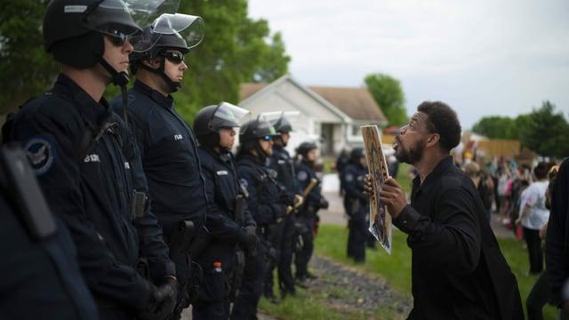 Polizisten in Vollmontur stehen Demonstranten gegenüber.