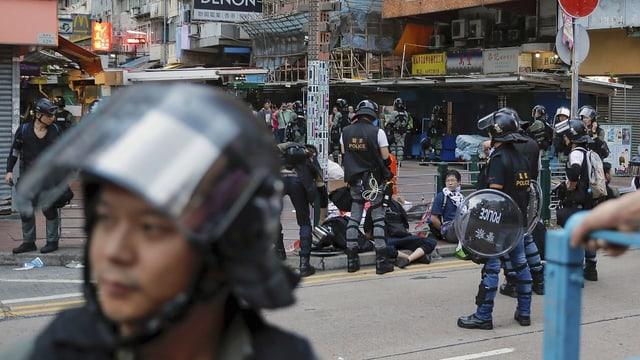 Überblick über Strasse mit Polizei und Protestierenden.
