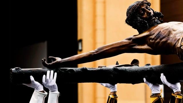 Jesusfigur auf dem Kreuz, wird von von Händen in weissen Handschuhen getragen.