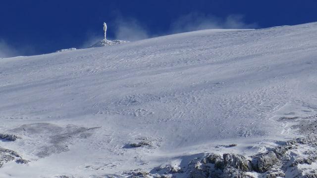 In der nähe des Muttsees liegt eine wenig Schnee, am Berghang steht ein Windmessgerät.