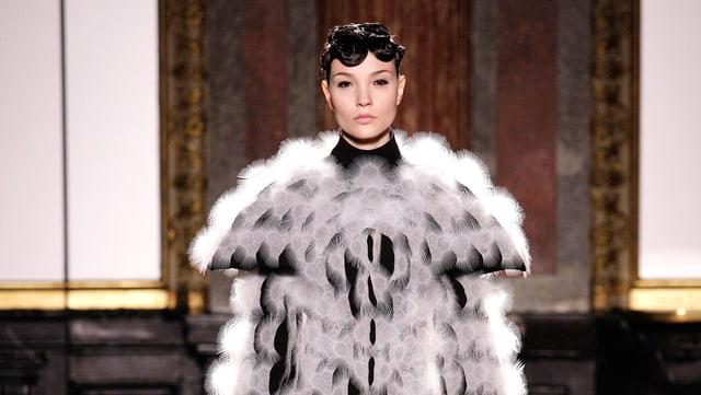 Ein Modell in einem Mantel, der auf den ersten Blick wie ein Pelzmantel aussieht, sich auf den zweiten aber als spannungsgeladenes Material entpuppt.